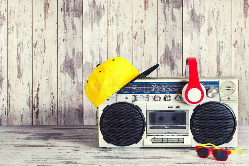 Begreppet av stilen för musikhöftflygtur Ljudsignal spelare för tappning med hörlurar, det trendiga locket och solglasögon royaltyfri bild