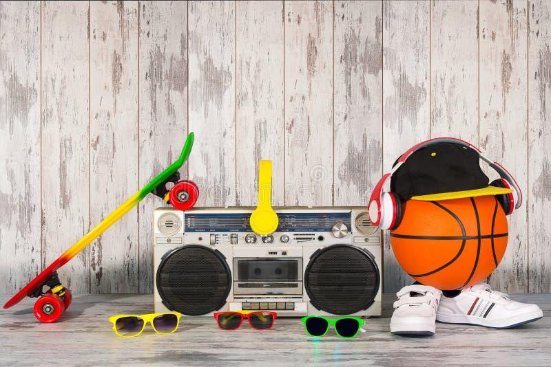 Begreppet av stilen och sportarna för musikhöftflygtur Ljudsignal spelare för tappning med hörlurar, trendigt lock, gymnastikskor royaltyfri fotografi