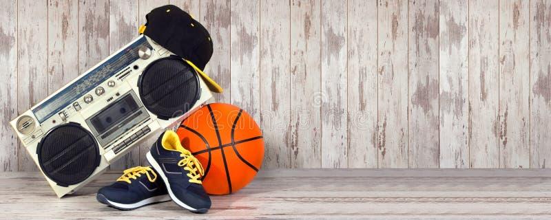 Begreppet av stilen och sportarna för musikhöftflygtur Ljudsignal spelare för tappning, trendigt lock, gymnastikskor och basketbo arkivfoton