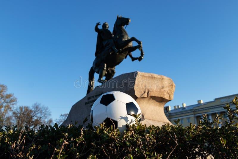 Begreppet av världscupen i St Petersburg Fotbollboll på bakgrund av bronsskickliga ryttaren Monument till grundaren av St P royaltyfri foto