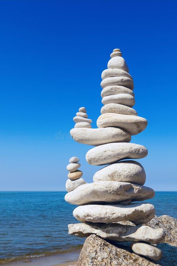 Begreppet balans och harmoni Vita stenar, frysta mot bakgrund av havet och blå himmel arkivbilder