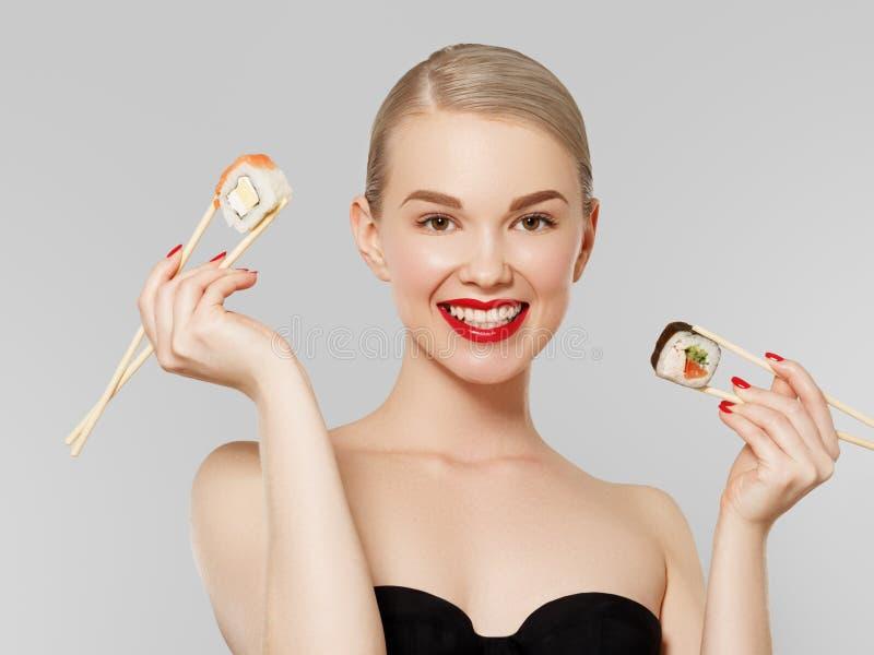 begreppet bantar h?lsa Sund japansk mat Den manicured härliga blonda flickan med röda kanter och spikar att äta sushi fotografering för bildbyråer