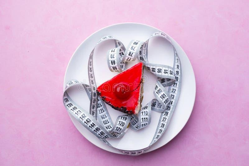 begreppet bantar söt körsbärsröd kaka och måttband fotografering för bildbyråer