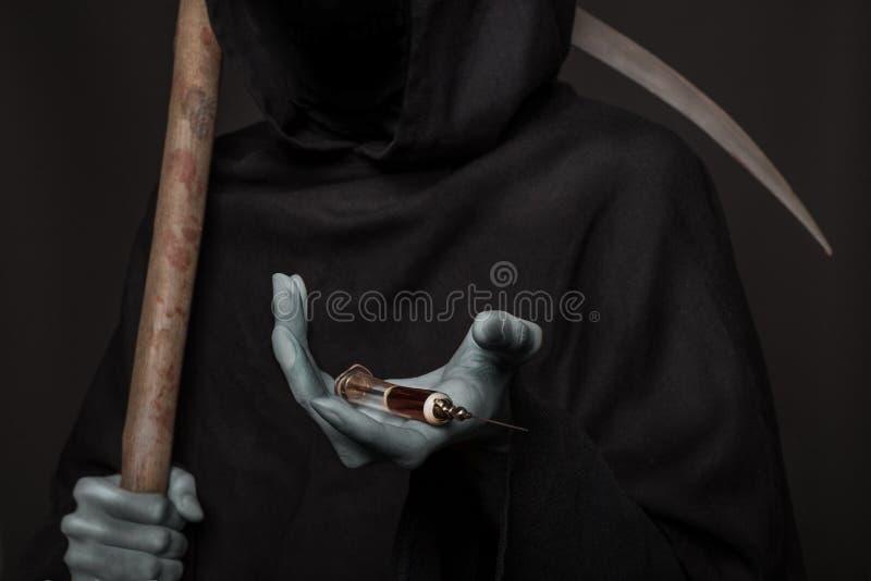 Begreppet: drogbyte Dödsängelinnehavinjektionsspruta med heroin arkivbilder
