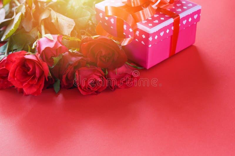Begreppet för förälskelse för blomman för asken för valentindaggåvan/den rosa gåvaasken med röda rosor för bandpilbågen blommar arkivbild