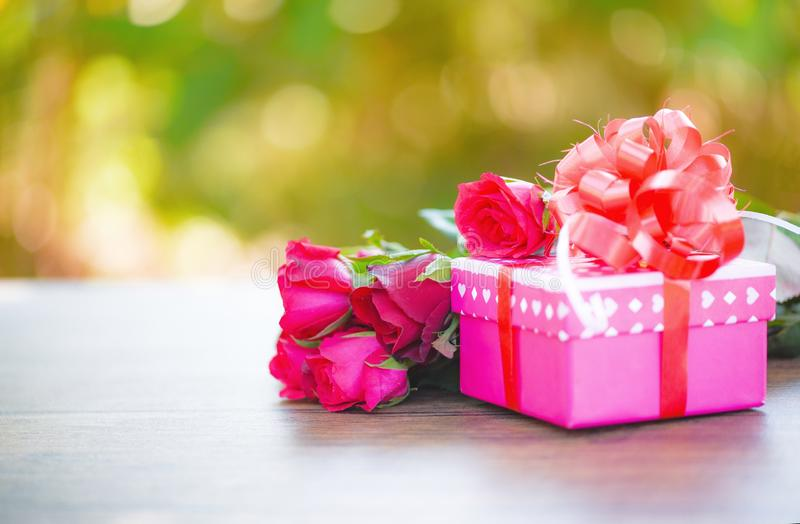 Begreppet för förälskelse för blomman för asken för valentindaggåvan/den rosa gåvaasken med röda rosor för bandpilbågen blommar arkivfoto