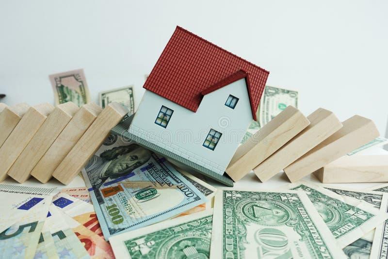 Begreppet för fastighetmarknadskollapsen med modellhuset kraschade vid dominobrickastycken arkivfoto