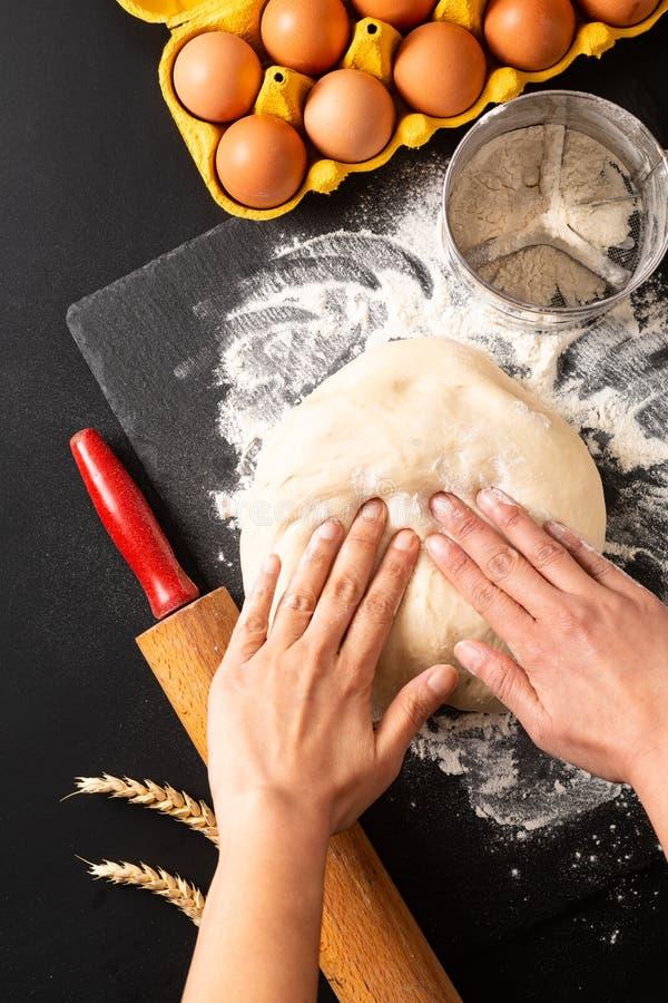 Begreppet för matförberedelsen sköt uppe i luften att knåda deg för bageri, pizza eller pasta på svart bakgrund med kopieringsutr fotografering för bildbyråer