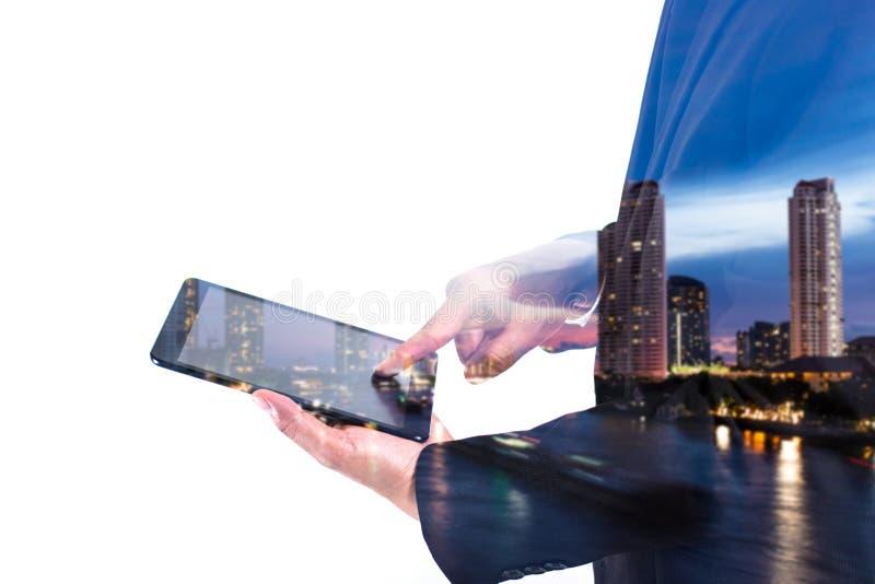 Begreppsaffärsman för dubbel exponering som bär den svarta dräkten och arbete med en digital minnestavla med modern stadsnattbakg arkivfoto