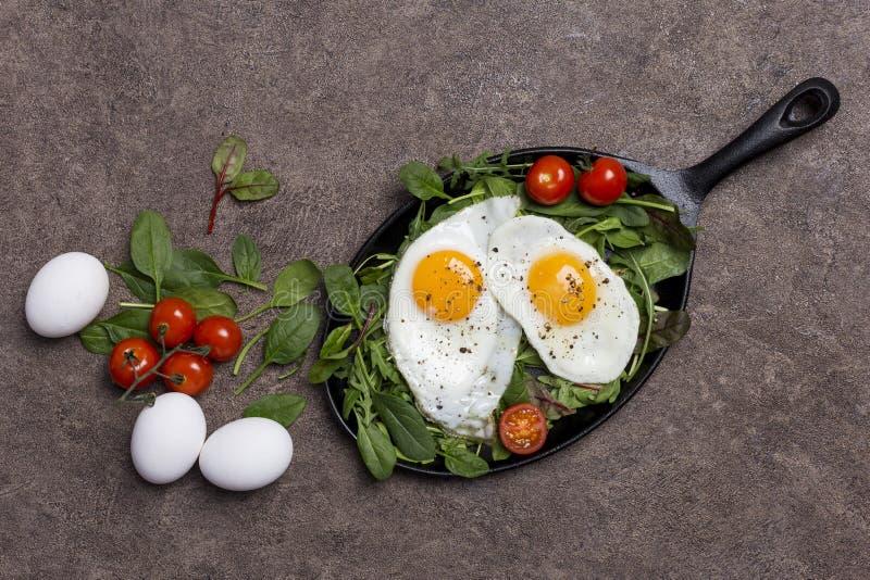 Begreppsbakgrund med stekte ägg, körsbärsröda tomater och ny gräsplan fotografering för bildbyråer