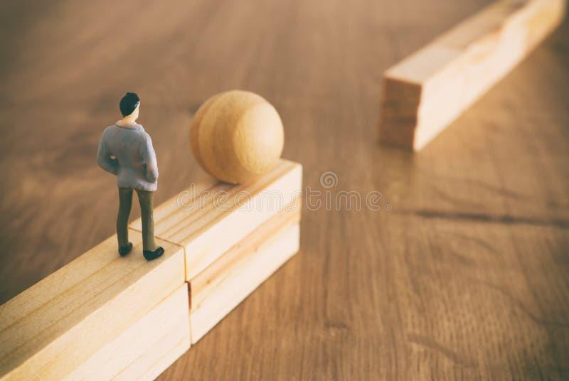 Begreppsbild av affären och utmaningen En man måste rulla en boll över en hög vägg och passera den över ett mellanrum Problemlösn royaltyfria bilder