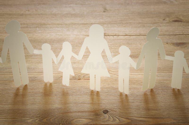 begreppsbild av händer för innehav för utklipp för familjpapperskedja, över trätabellen royaltyfria foton