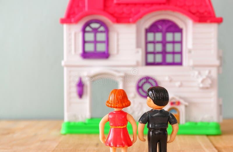 Begreppsbilden av barn kopplar ihop framme av nytt hus små plast- leksakdockor (mannen och kvinnlign), selektiv fokus arkivfoto