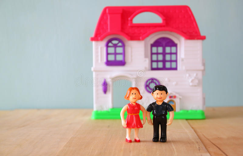 Begreppsbilden av barn kopplar ihop framme av nytt hus små plast- leksakdockor (mannen och kvinnlign), selektiv fokus royaltyfri foto