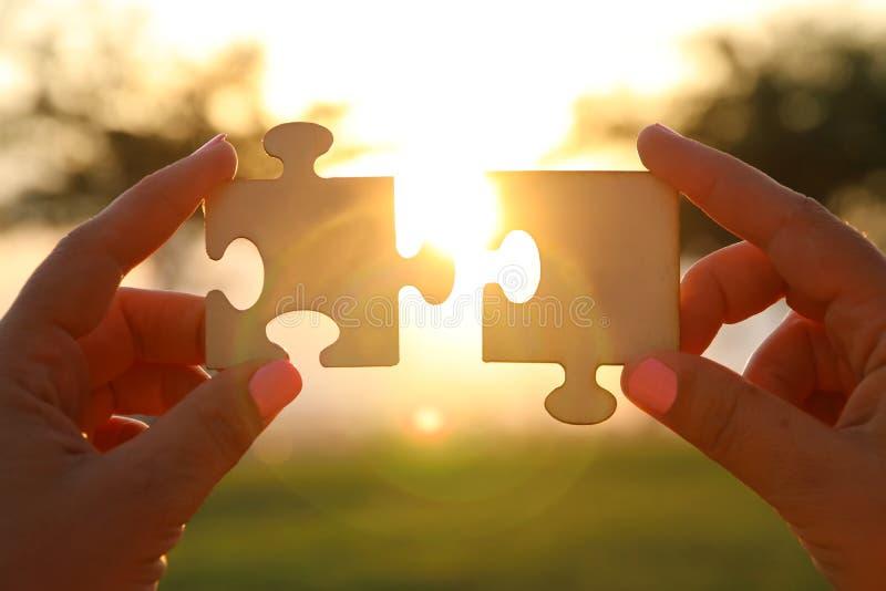 Begreppsbilden av en kvinna räcker att rymma två stycken av ett pussel främsta av solen solnedgångtid med linssignalljuset kreati arkivbild