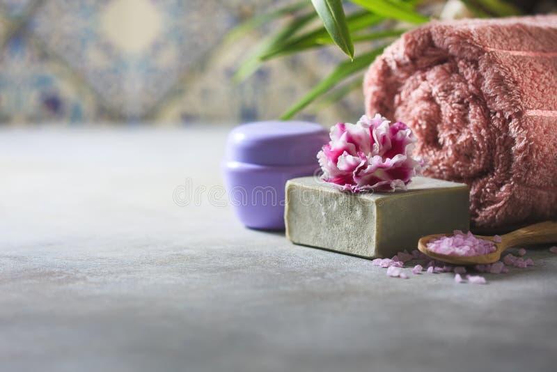 Begreppsbrunnsorten Handgjord salta tvål, handdukar, blommor och hav royaltyfri bild