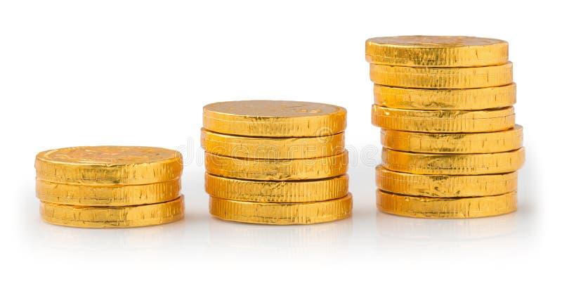 Begreppsframgång i affären, bunt av guld- mynt som isoleras på en vit bakgrund arkivfoto