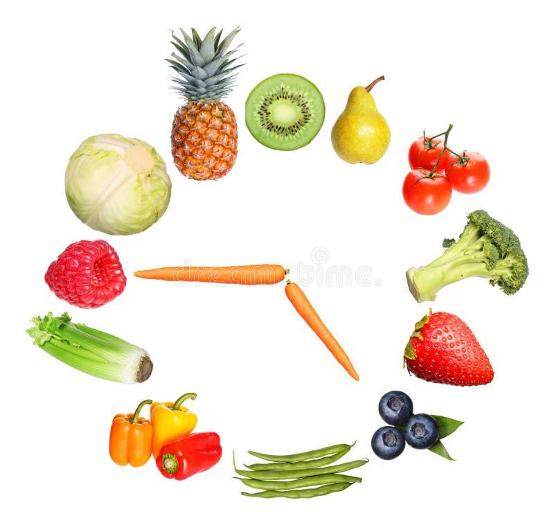 Begreppsfrukter och grönsaker tar tid på isolerat på vit royaltyfri fotografi