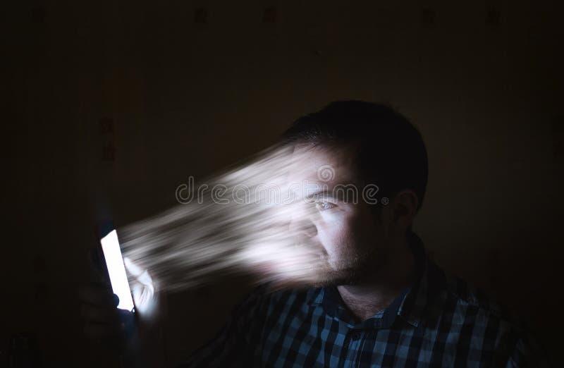Begreppsinternet av beroende, undergivenhet Mannen sög in i en telefon Framsidan för man` s överförs till smartphonen royaltyfri fotografi