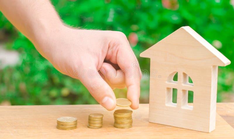 Begreppsinvestering i fastighet Sparande pengar som köper ett nytt hem Trähus och buntar av mynt från litet till stort Köpande r royaltyfri foto