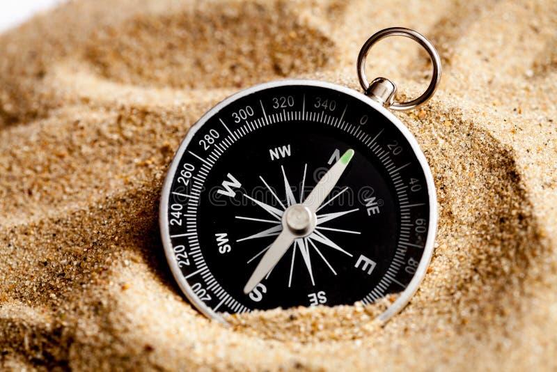 Begreppskompass i sand som söker betydelse av liv royaltyfri fotografi