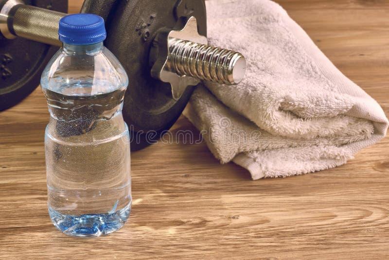 Begreppskonditionutrustning med hanteln, flaska av vatten och handduk arkivbilder