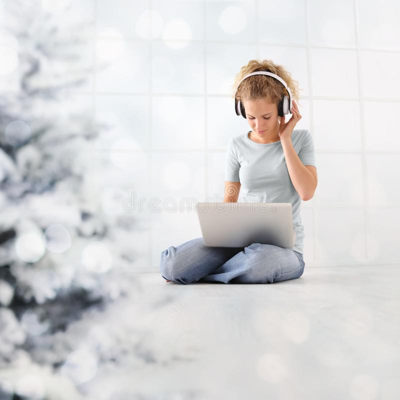 Begreppskvinnan för glad jul på datoren med hörlurar som bläddrar internet, lyssnar till musik eller ser en film att sitta på arkivfoton