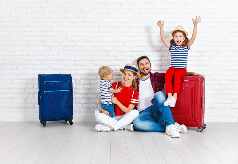 Begreppslopp och turism den lyckliga familjen med resväskor near w royaltyfria foton