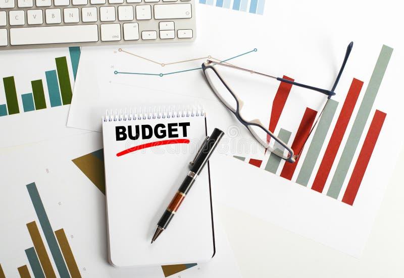 Begreppsmässig bakgrund med ordbudgeten som är skriftlig i anteckningsboken som är bredvid ekonomi, tangentbordet, kulspetspennan fotografering för bildbyråer