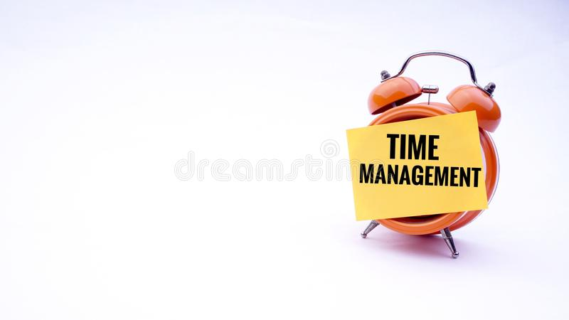 Begreppsmässig bild av affärsidéen med ordTid ledning på en klocka med en vit bakgrund Selektivt fokusera arkivbild