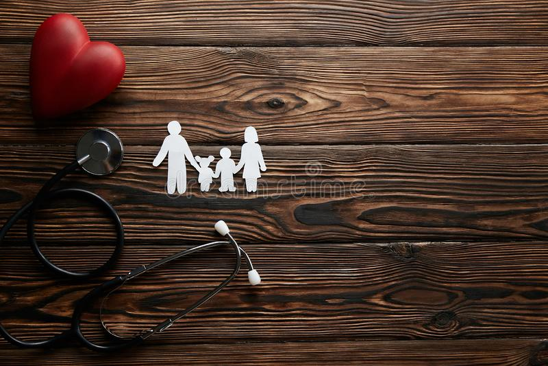 Begreppsmässig bild av den pappers- kedjan i form av familjen vård- insuarancetillbehör arkivbild