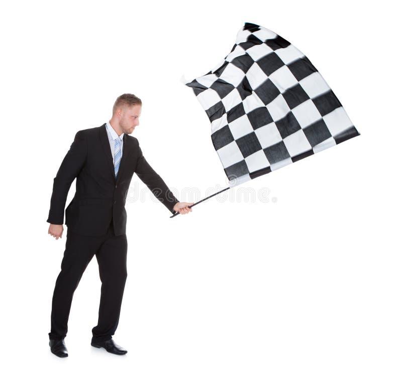 Begreppsmässig bild av en stilfull ung affärsman som vinkar en flagga royaltyfria bilder