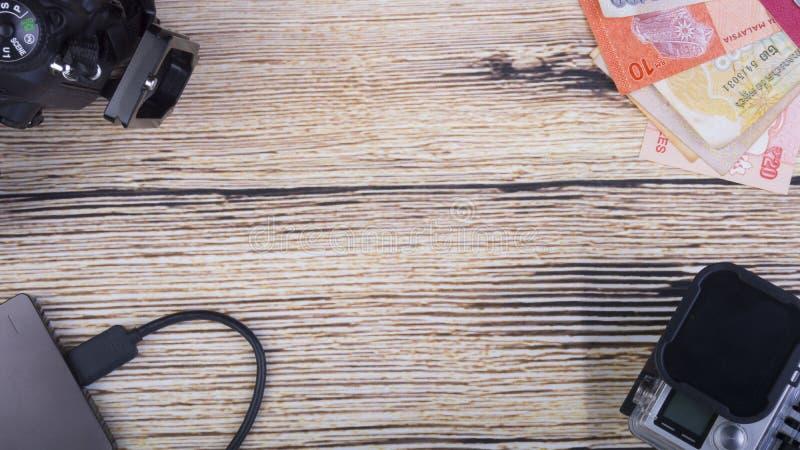 Begreppsmässig bild av feriebegreppet med kameran, massmedialagring, sedlar, minnestavlan och klockan på en träbakgrund royaltyfri fotografi