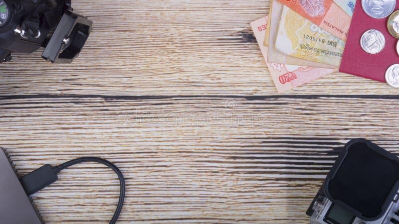 Begreppsmässig bild av feriebegreppet med kameran, massmedialagring, sedlar, minnestavlan och klockan på en träbakgrund royaltyfria bilder