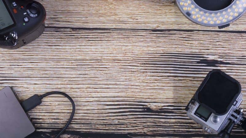 Begreppsmässig bild av feriebegreppet med kameran, massmedialagring, sedlar, minnestavlan och klockan på en träbakgrund fotografering för bildbyråer