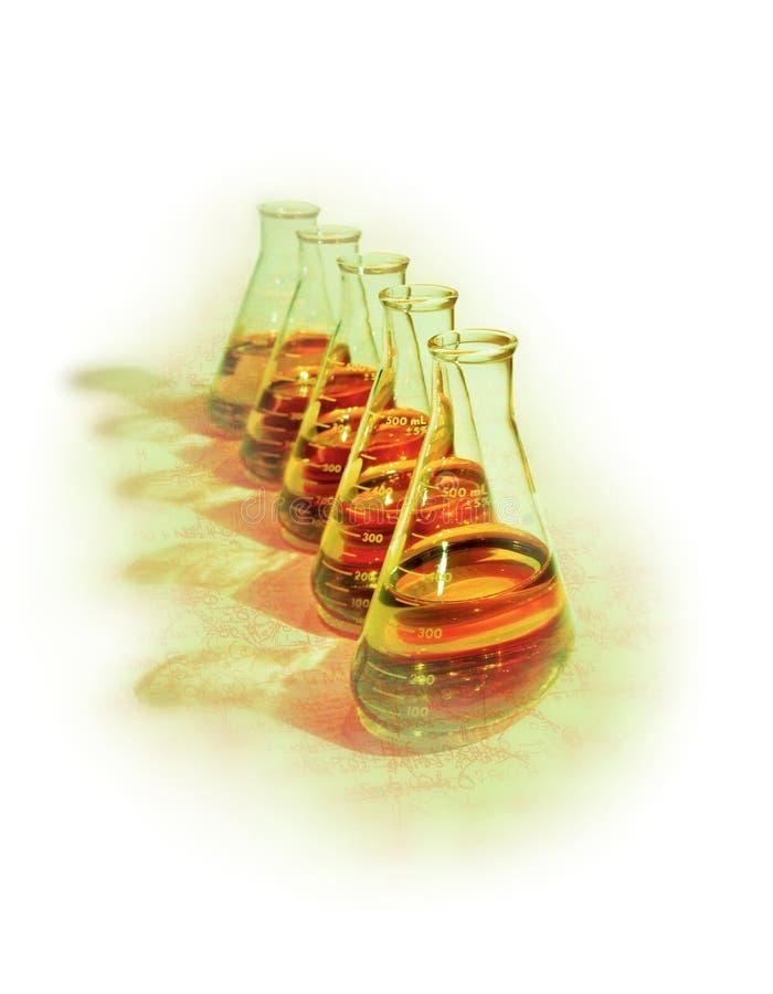 Begreppsmässig bild av raden av kemiska flaskor med orange lösningar på grön yttersida med subtila kemiska formler i bakgrunden royaltyfria foton