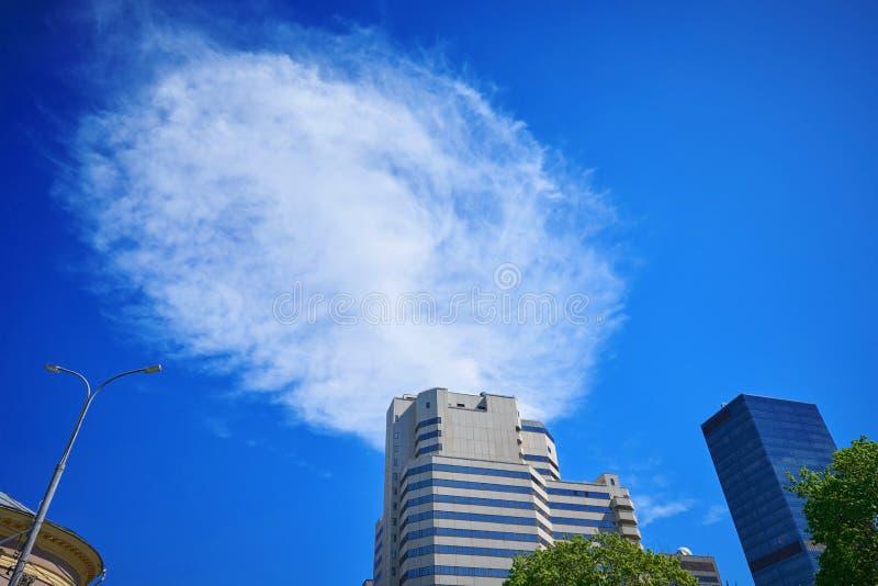 Begreppsmässig bild för abstrakt arkitektur Stort vitt moln i blå himmel som trycker på överkanten av kontorsbyggnaden Moln som r arkivbilder