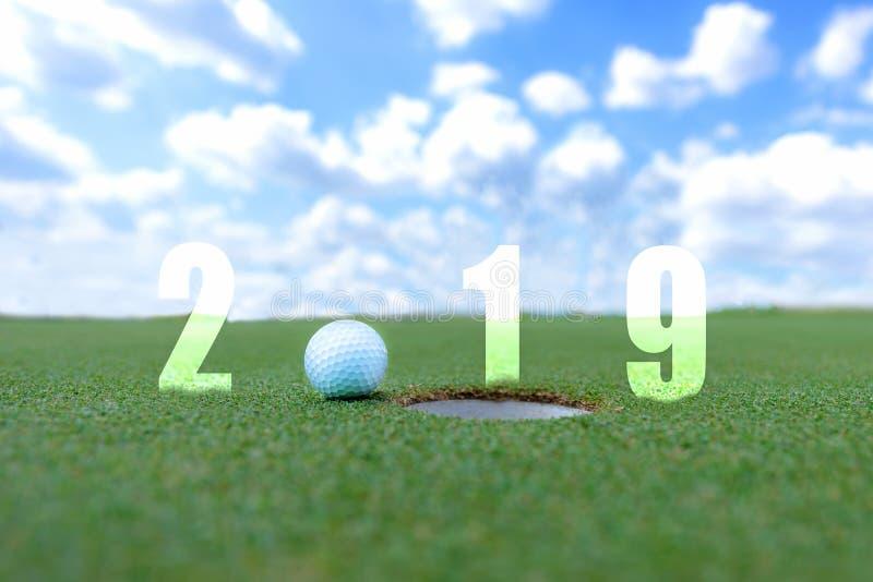 Begreppsmässig bild för golfsport Lyckligt nytt år 2019 Golfboll på den gröna farleden, bakgrund för blå himmel royaltyfri bild