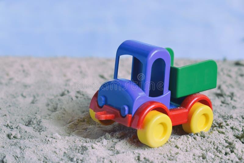 Begreppsmässig fotobild av den plast- bilen i öken Leksak för barn` s Barnlek i sanden Begreppet av en lycklig barndom K royaltyfri fotografi