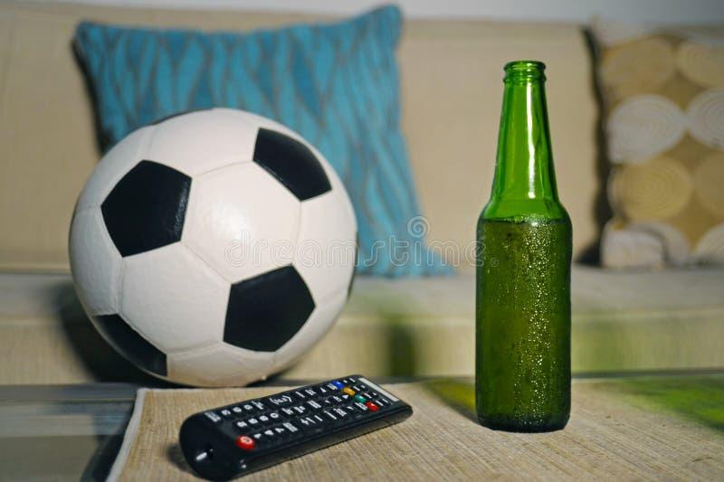 Begreppsmässig hållande ögonen på fotbolllek på soffan på television med ölflaskan och popcorn att bowla i vänner som tycker om T royaltyfria foton