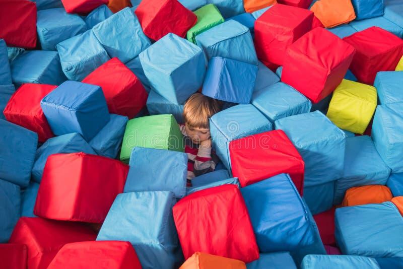 Begreppsmässig psykologi för barn för barnautism Pojke som täckas upp med färgrika mjuka kvarter, kuber Fysiologiska barn och royaltyfri fotografi