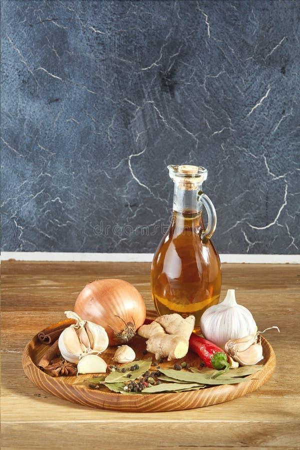 Begreppsmässig sammansättning av olika kryddor och olja skorrar på ett trämagasin på den lantliga tabellen, closeupen, selektiv f arkivbild