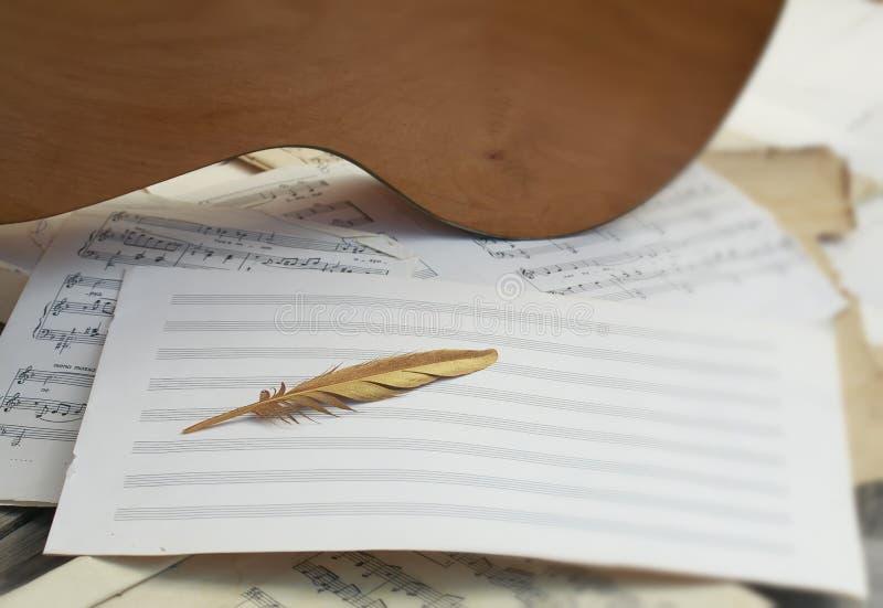 begreppsmässig sammansättning av trägiaran, ett symbol av de guld- fåglarna av en fjäder som ligger på en bakgrund av musik och arkivbilder
