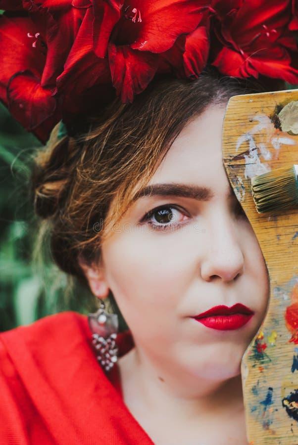 Begreppsmässig stående av den härliga kvinnakonstnären med röda kanter, röda blommor i hår som bakifrån ser av paletten arkivfoto