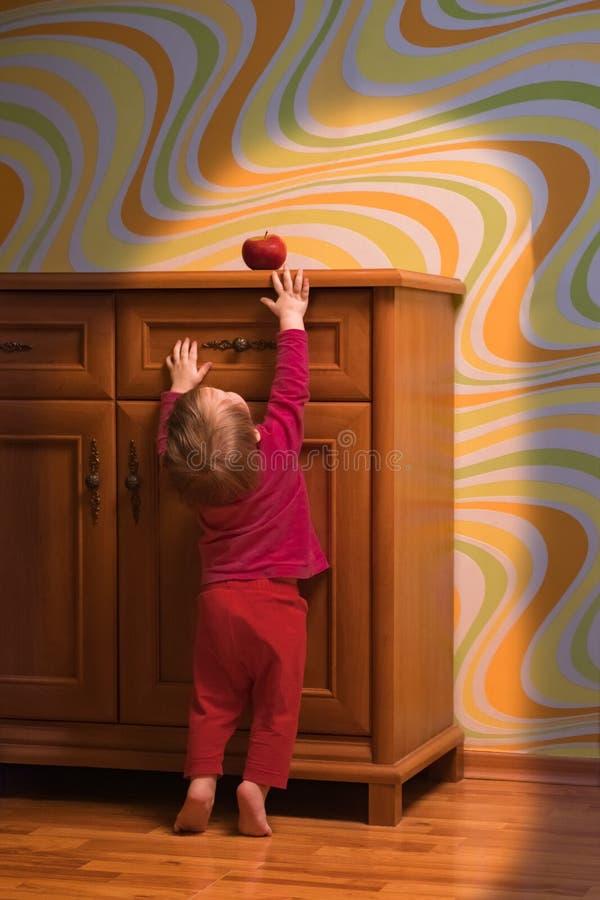 Begreppsmässig ståndaktighet Behandla som ett barn näringbegreppet Litet barn som försöker att nå det röda äpplet Lyckligt mål fö royaltyfri fotografi