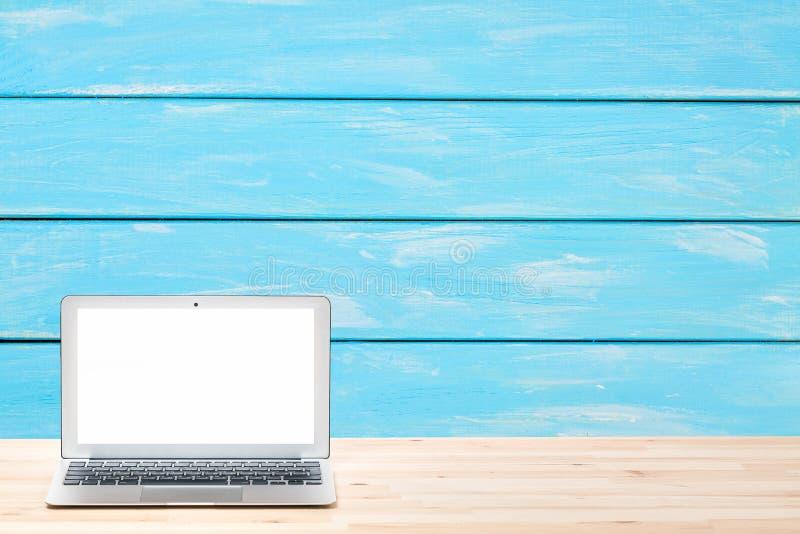 Begreppsmässig workspace eller affärsidé Bärbar datordator med den tomma vita skärmen på den ljusa trätabellen mot blå träväggnol arkivbilder
