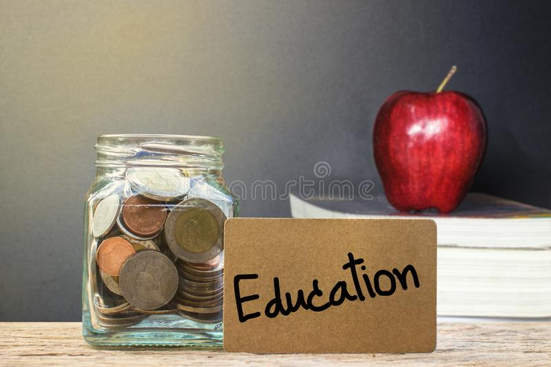 Begreppsmässiga sparande pengar för utbildning med det suddiga röda äpplet på royaltyfri bild