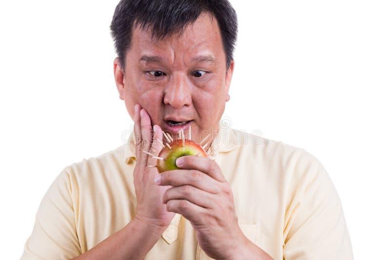 Begreppsmässigt av det hållande äpplet för mannen med taggskräck lida toothach arkivfoton