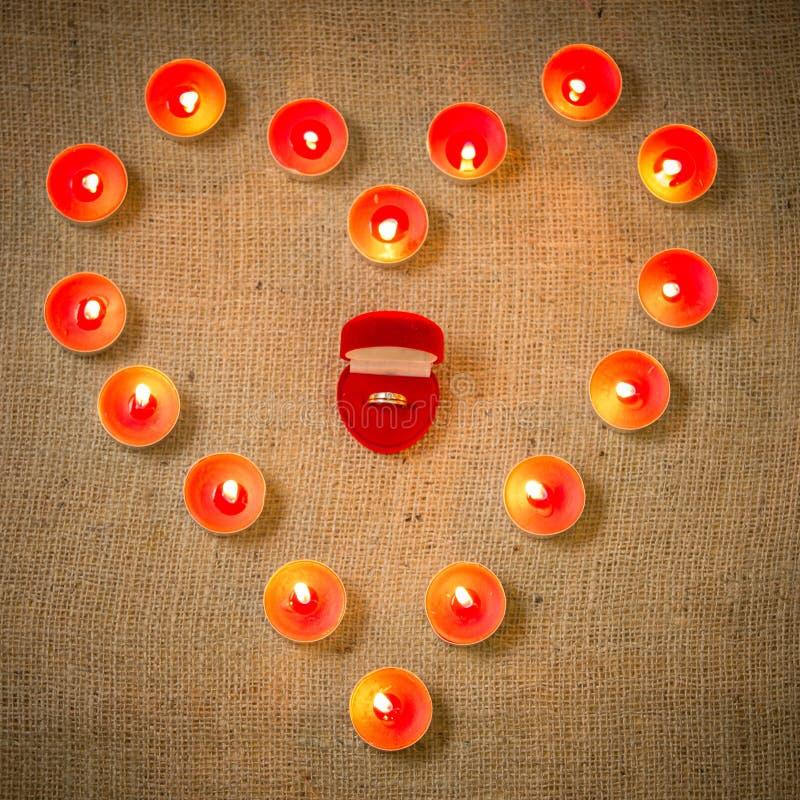 Begreppsmässigt foto av vigselringen som omges av stearinljus i form royaltyfri fotografi