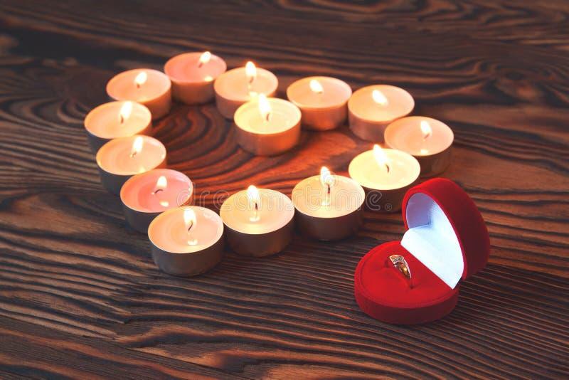 Begreppsmässigt foto av vigselringwitnstearinljus i form av hjärta arkivfoton